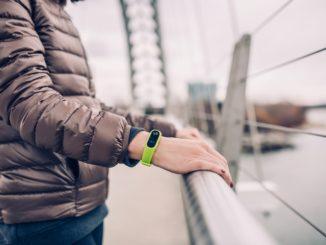 Eine Smartwatch am Gelenk einer jungern Frau.