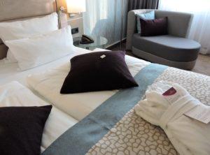 Hotelzimmer, Betten mit mehreren Kopfkissen und Bademantel