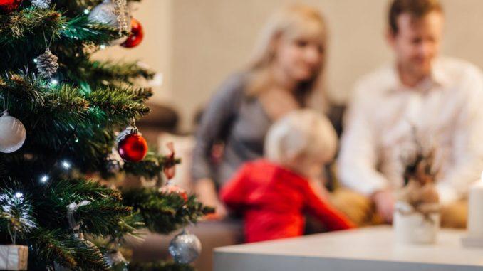 familie-weihnachten-mit-weihnachtsbaum-links-kleines-kind-frohes-fest