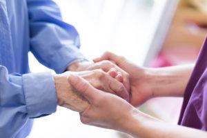 Pflegerin hält älterer Dame die Hände.